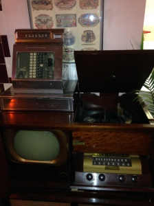 Clockwise from top left: cash register, record player, television, and radio, all very vintage.